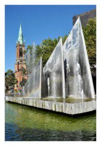 Postkarte mit Blick auf den Düsseldorfer Mack Brunnen, im Hintergrund die Johanneskirche